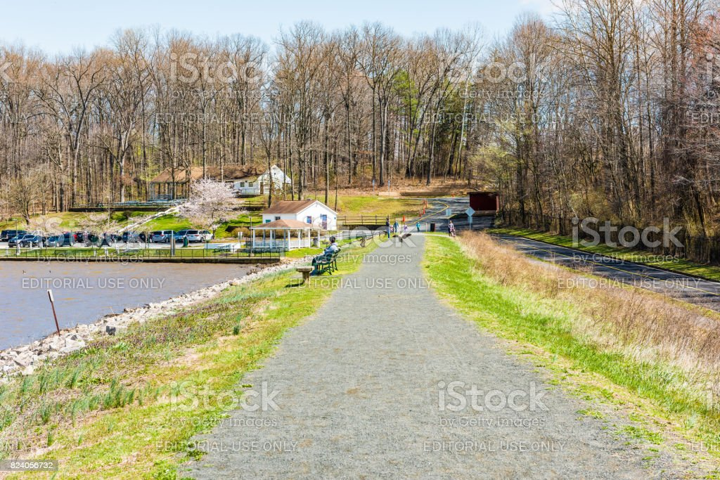 Trail in Accotink park with people sitting on benches in spring by lake stock photo