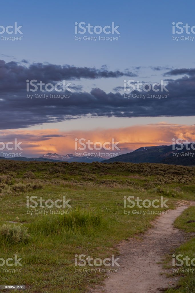 Trail Leads Into Field and Sunset stock photo