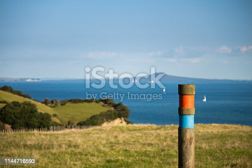Landscape scene of coastal cliffs and distant volcano, focusing on a trail marker post