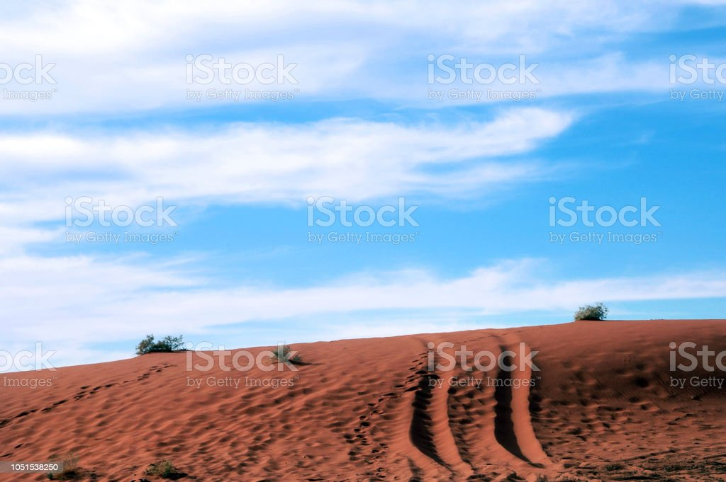 4WD trail marks on a red Sand dune under blue sky stock photo