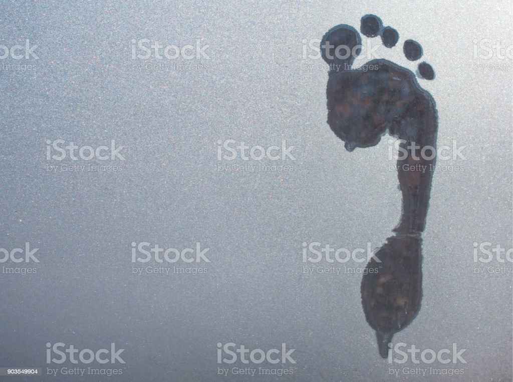 trail of a bare foot on frozen glass stock photo
