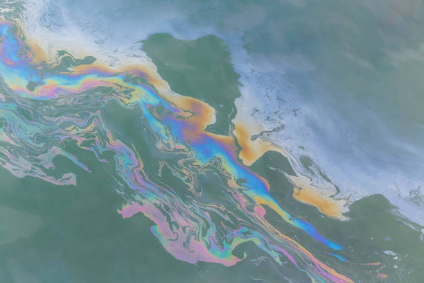 trail of oil on water in ocean creating a colourful trail stock photo