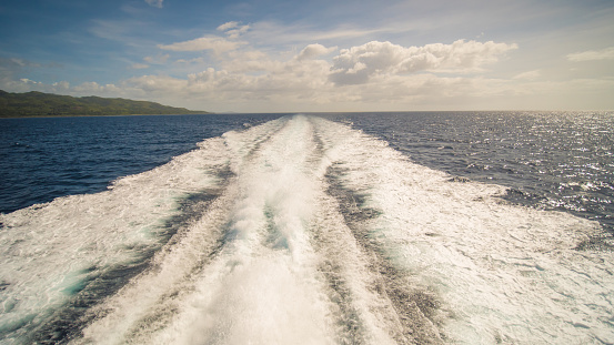 A trail of sea water foam follows the ferry to the island of Palawan. Philippines. Shooting in motion