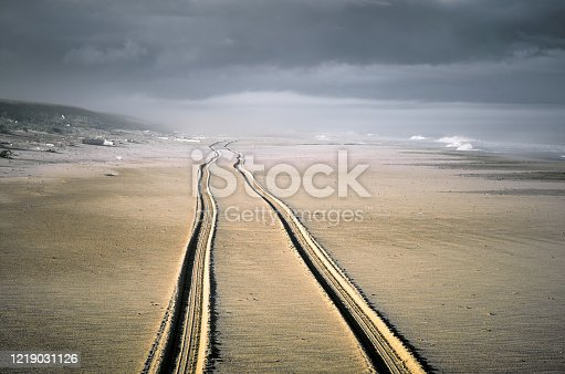 Trail of two wheels of car drove along the wide beach. Coastline sea and dark cloudy sky