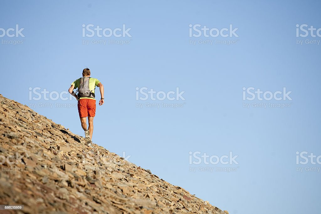 A trail runner ascending a mountain. royalty-free stock photo