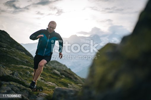 He is on a high mountain path with dramatic sky and clouds behind