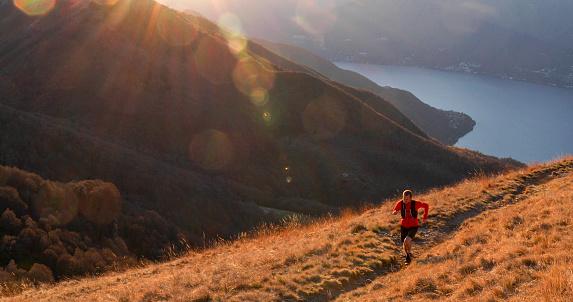 Trail runner crosses mountain ridge in the morning