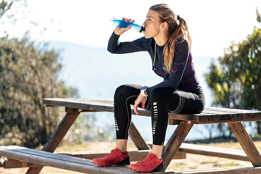 Trail runner drinking water while sitting on bench for relaxing one moment on mountain peak.