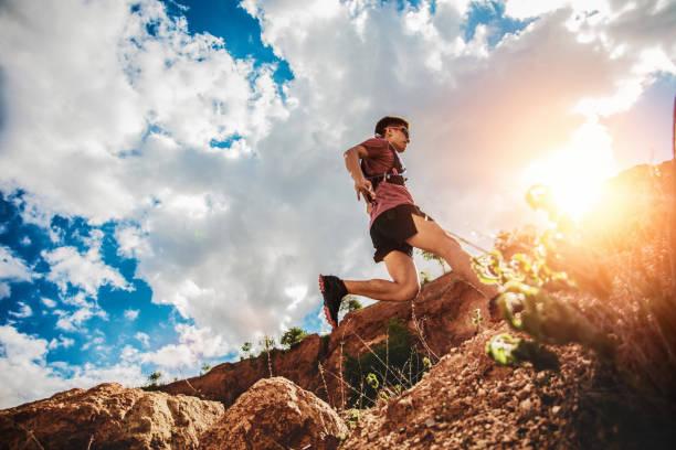 corredor de trail saltando en el horizonte y la piedra - foto de stock