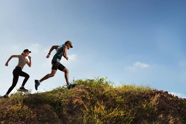 trail runner of men and women running on the mountain - carpet runner stock photos and pictures