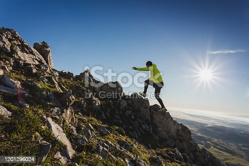 Trail runner man running and climbing on mountains. Great landscape at background . Active health and motivation lifestyle