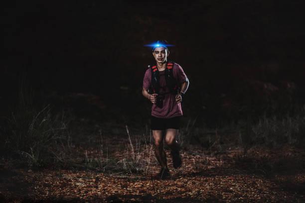 corredor de trail corriendo en el camino rocoso en la noche - foto de stock