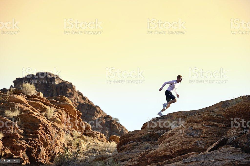 Trail runner sprinting on horizon stock photo
