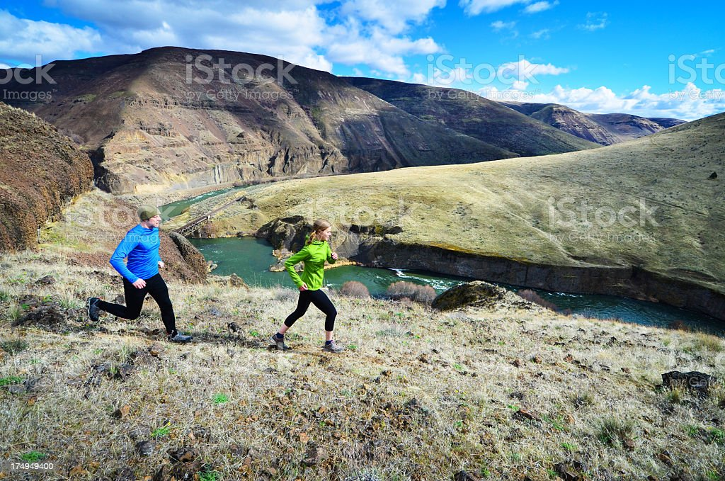 Trail runners running beside water ravine through mountains royalty-free stock photo