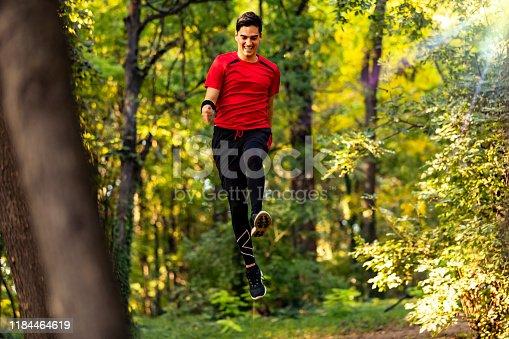 485902386istockphoto Trail running big jump 1184464619