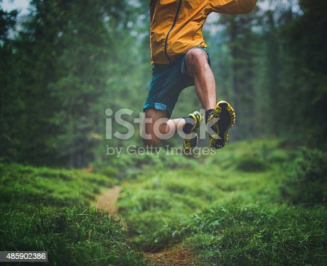 A man exercise trail running in a green and wet forest, jumping over tree roots.
