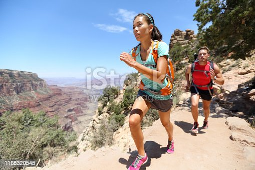 Trail running cross-country runners in race on path in Grand Canyon, USA. Fit athletes jogging and training together in beautiful nature landscape. Asian fitness woman, Caucasian fit model.