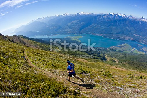 A man goes trail running near Revelstoke, British Columbia, Canada. He is wearing a running vest that carries two water bottles.