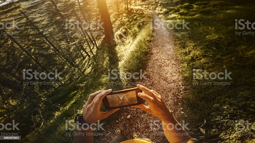 POV Trail running in the forest: checking map on mobile stock photo