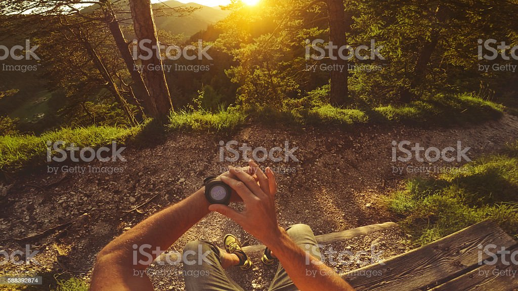 POV Trail running in the forest: checking smart watch stock photo