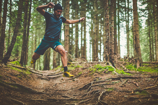Trail running in the forest: jumping roots