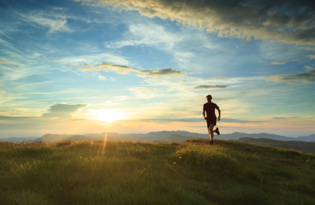 Trailrunning Athlete trailrunning in the mountains during a nice sunset. With motionblur. horizon over land stock pictures, royalty-free photos & images