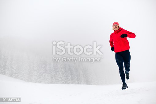 484750230 istock photo Trail running woman on snow in winter mountains 924837766