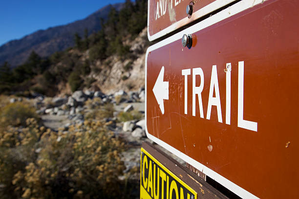 Trail Sign Sign pointing to Trail and Caution beneath for flash floods in a creek area of San Bernardino Mountains redlands california stock pictures, royalty-free photos & images