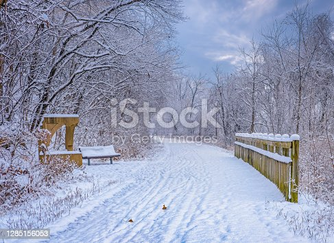 View of snow covered trail with wooden bridge and trees on both sides; sky in the distance; Missouri River bluffs on left