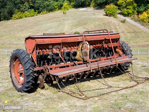 Trailed seeder for crops stands in the field