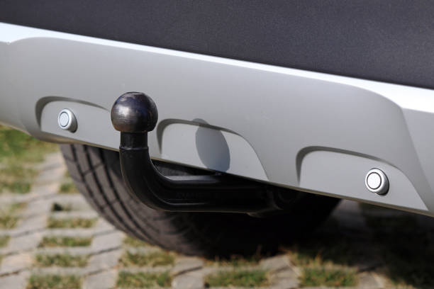 Trailer coupling on a silver-coloured car with reverse warning devices Trailer coupling on a silver-coloured car with reverse warning devices coupling device stock pictures, royalty-free photos & images