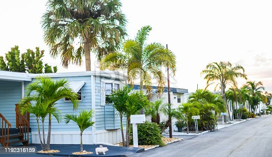Mobile homes or trailer homes in a suburban middle American neighborhood development. Homes are  nice, neat and and modest in a pleasant looking development or neighborhood. Residential lower middle class Mobile  homes in a planned park or community