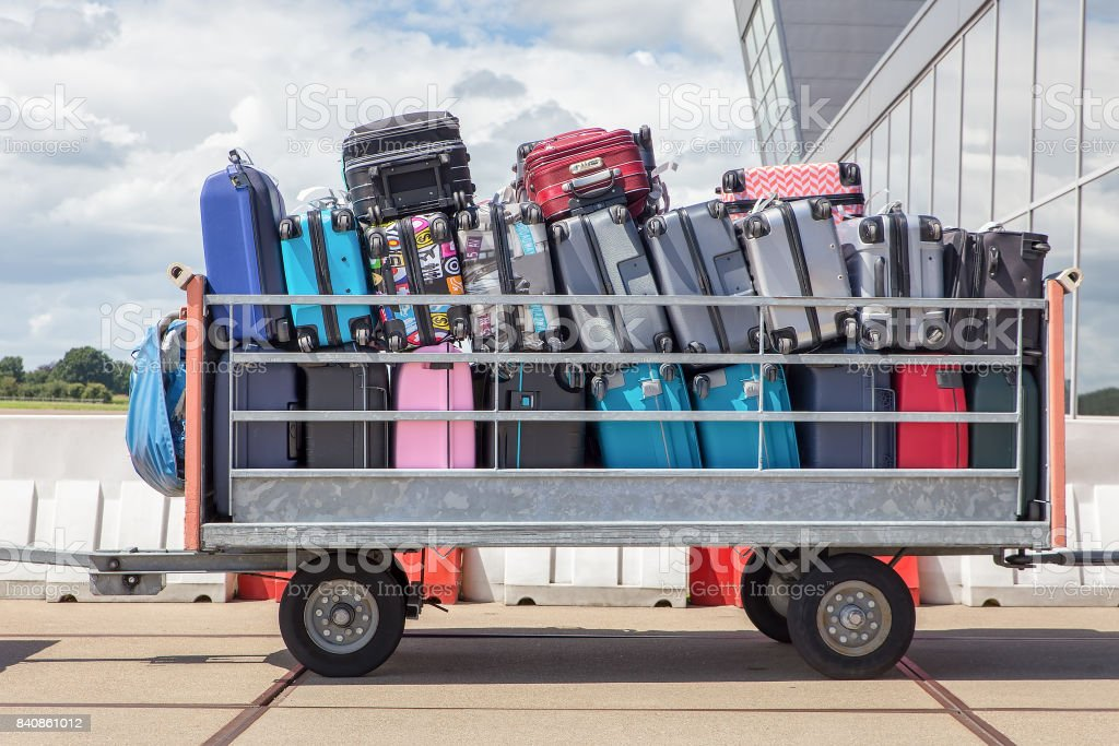 Trailer on airport filled with suitcases stock photo