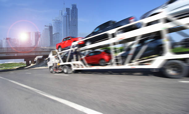 Trailer transports cars on highway with big city background stock photo