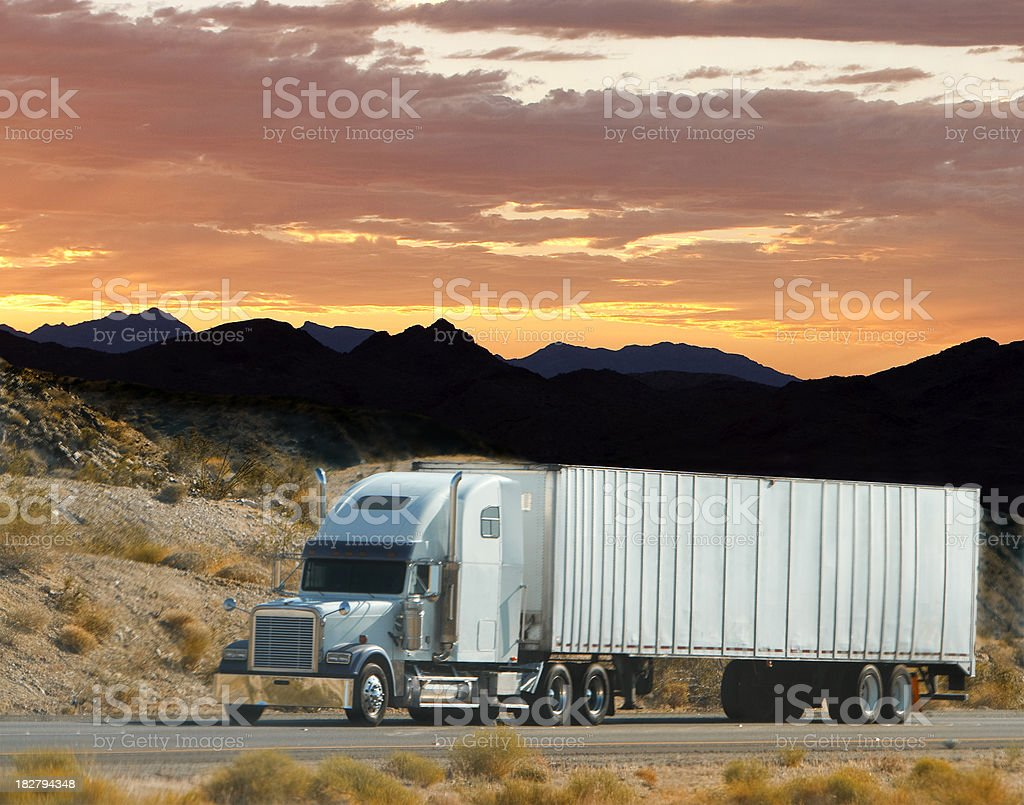 Trailer truck traveling on the road at sunset royalty-free stock photo