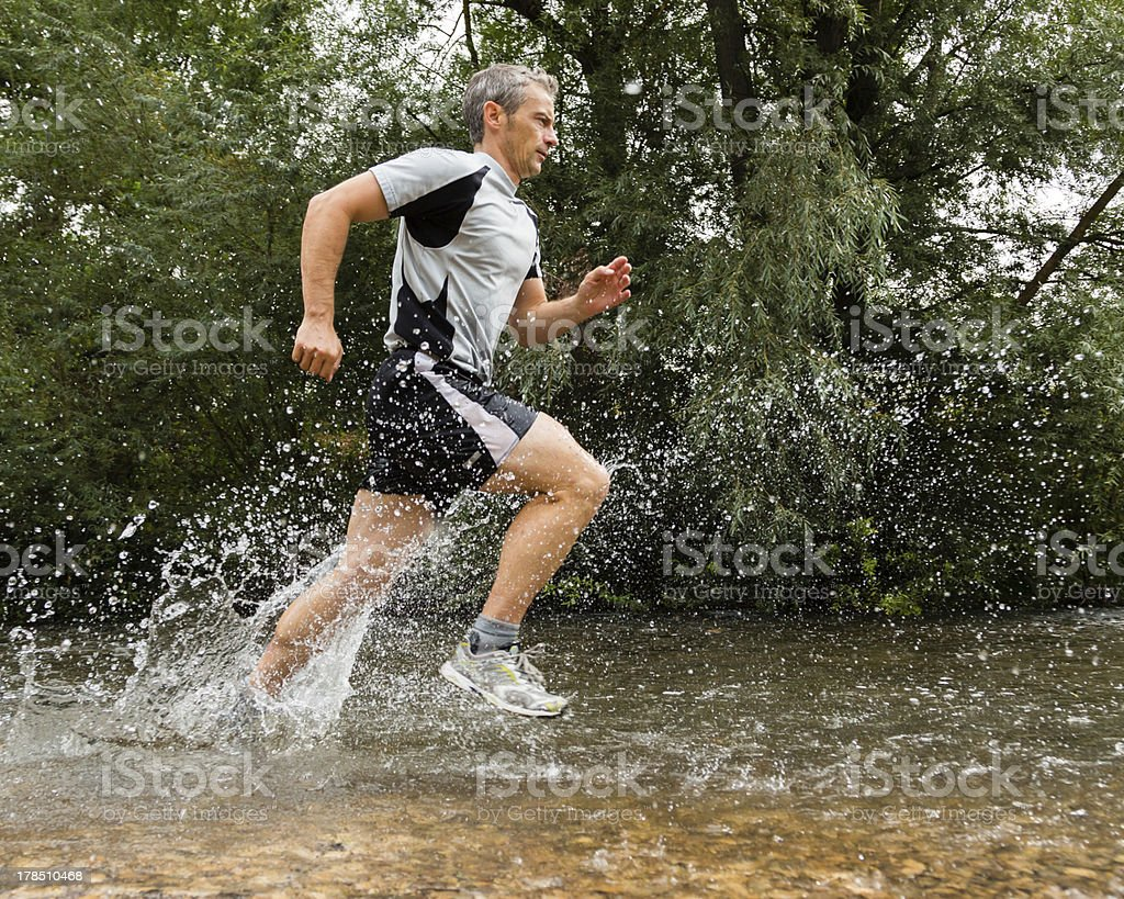trailrunning through a streambed stock photo