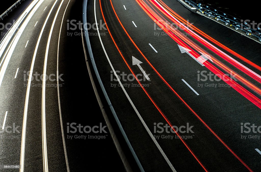 trails lines line red white asphalt road arrow direction night stock photo