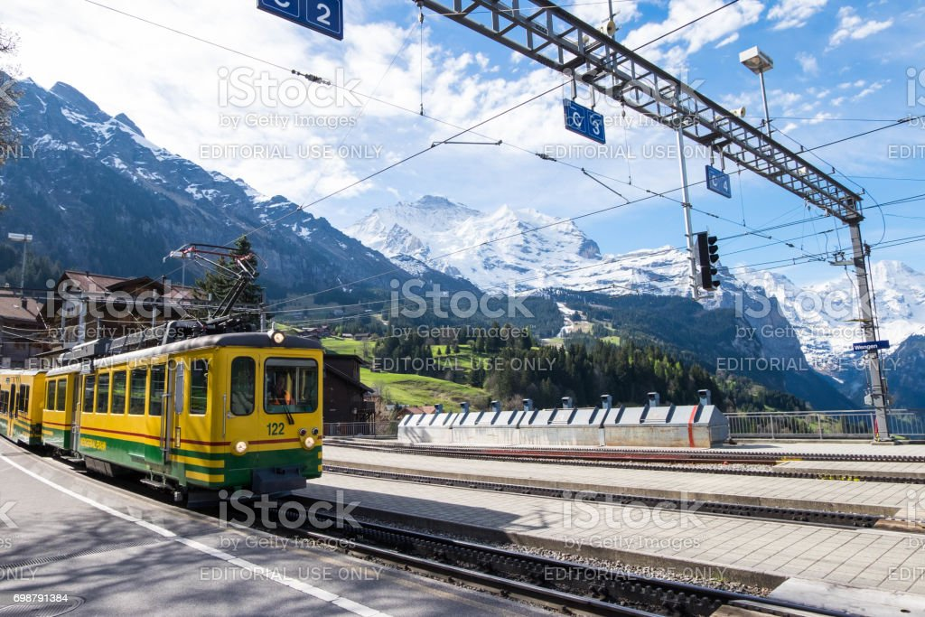 train about to stop at Wengen station. Alps and nature as beautiful background of it. stock photo