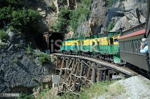 A narrow gauge train enters a tunnel in the Rocky Mountains.