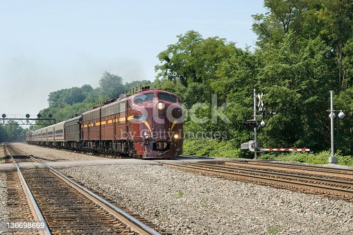 Train at grade crossing, diesel locomotives pulling a toursit excursion on the old PRR mainline at Altoona, Pennsylvania, PA, USA.
