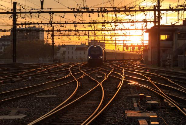 train au crépuscule - transport ferroviaire photos et images de collection