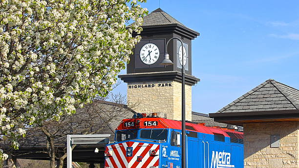 Train at station with clock tower and spring tree blossoms stock photo