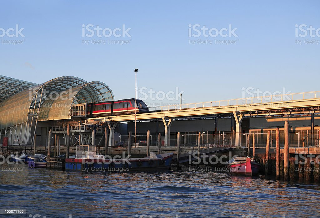 Train Between Sea And Sky Modern train moving from glass monorail station over sea. Venice, Italy Bridge - Built Structure Stock Photo