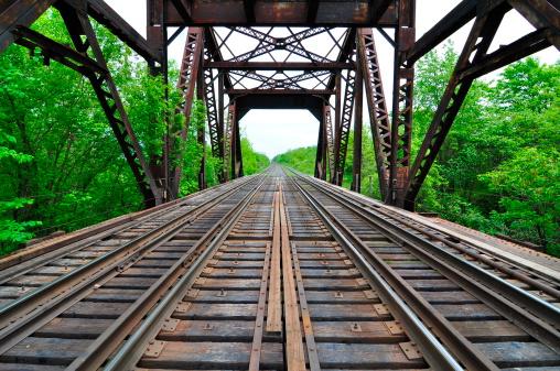 Looking down some long train tracks starting at a train bridge.