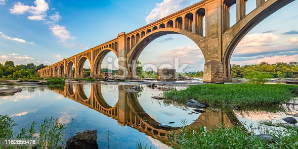 The Atlantic Coast Line train bridge in Richmond, Virginia casts a reflection on the James River below.