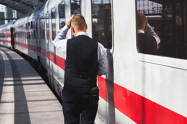 train conductor from behind standing at station - transport conductor stock photos and pictures