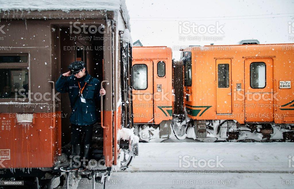 Oficer konduktor pociągu jazdy na vintage potbelly piec pociąg opperated na kolei Tsugaru w śniegu zimą na stacji Goshogawara, Aomori, Tohoku, Japonia. - Zbiór zdjęć royalty-free (Azja)