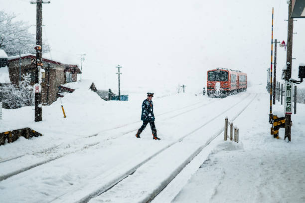 train conductor officer walk cross tracks on tsugaru railway in winter snow at goshogawara station. - goshogawara zdjęcia i obrazy z banku zdjęć