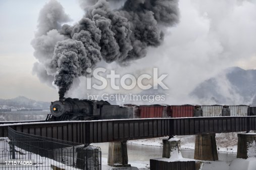 Train crossing bridge over river in winter with tall smoke plumes in the cold air, an old steam railroad locomotive with vintage freight cars, Cumberland, Maryland, MD, USA.