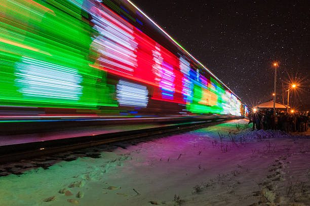 Train Decorated with Holiday Lights Arrives at Station stock photo
